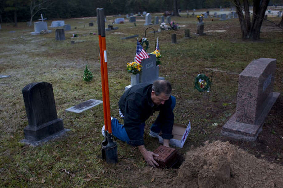 Travis Jones buries the ashes of his brother Claude during a service Tuesday at White Oak Cemetery in Porter. Photo: Johnny Hanson, Houston Chronicle