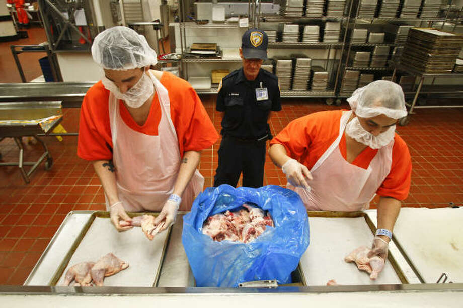 Inmates Chris Thibodaux, left, and Santos Florez prep chicken for the Thanksgiving meal as food services technician Eugene Hutchins supervises at the Harris County Detention Center's kitchen Wednesday. Photo: Michael Paulsen, Chronicle