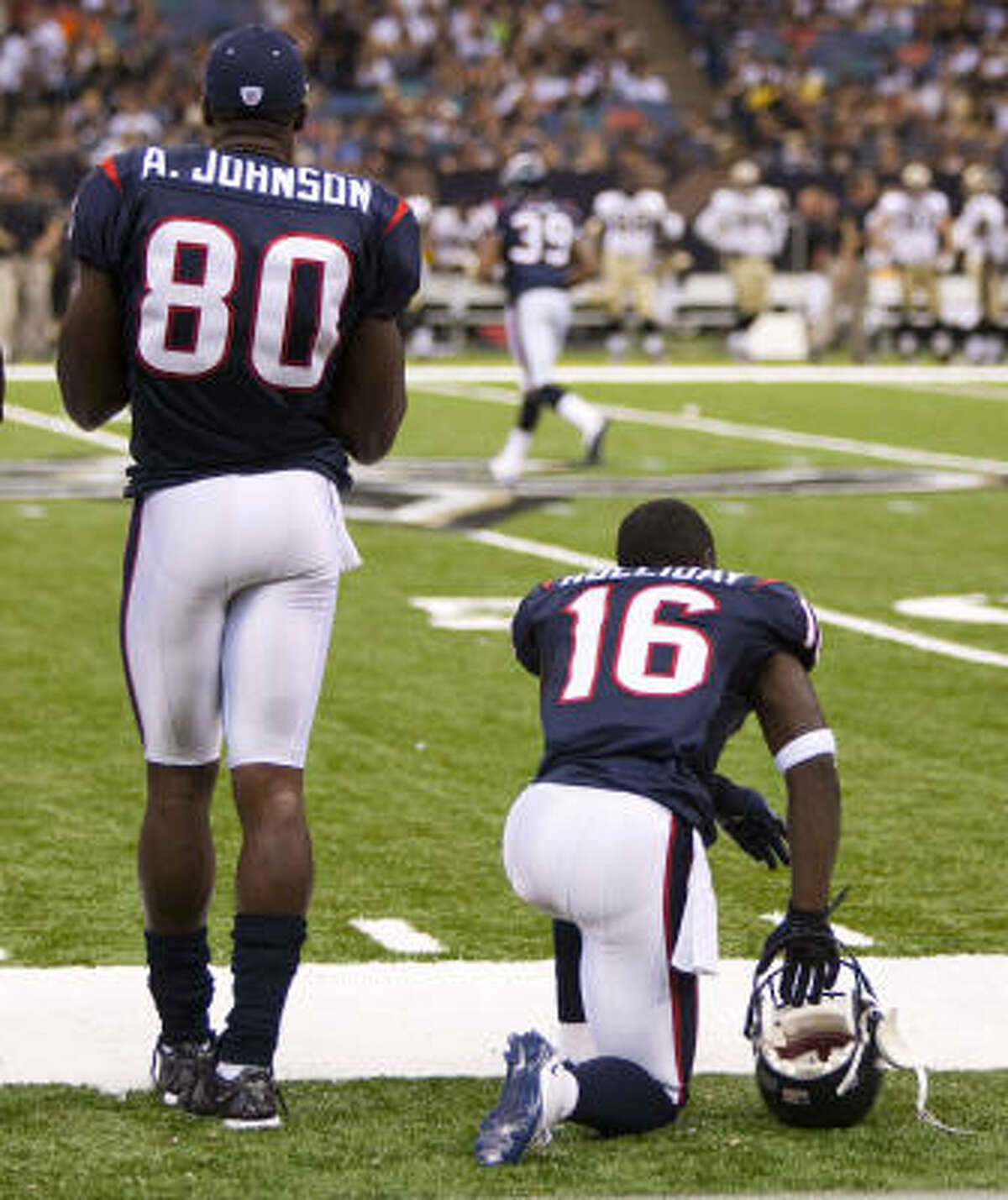 The Texans' Trindon Holliday kneels on the sidelines next to receiver Andre Johnson during the third quarter of a preseason game against the Saints.