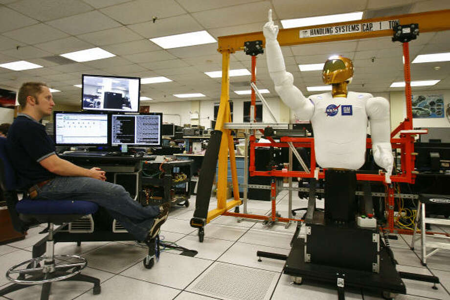 John Yamokoski, a Control Engineer with NASA, demonstrates the R2's mobility. NASA hopes one day to use humanoid robots for spacewalks. GM wants to adapt them for assembly line tasks. Photo: Michael Paulsen, Chronicle