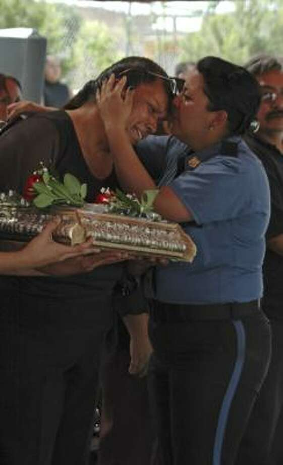 A police officer embraces an unidentified relative of policeman Jose Alan Valenzuela, during a funeral at the police station in the northern border city of Ciudad Juarez on Wednesday. Photo: Associated Press