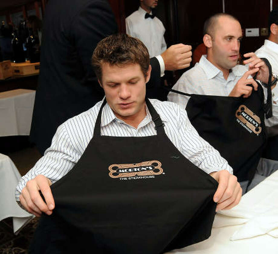 David Anderson and Matt Shaub dawn waiters aprons during a fundraiser for the Catch a Dream Foundation at Morton's Steakhouse. Photo: Dave Rossman, For The Chronicle