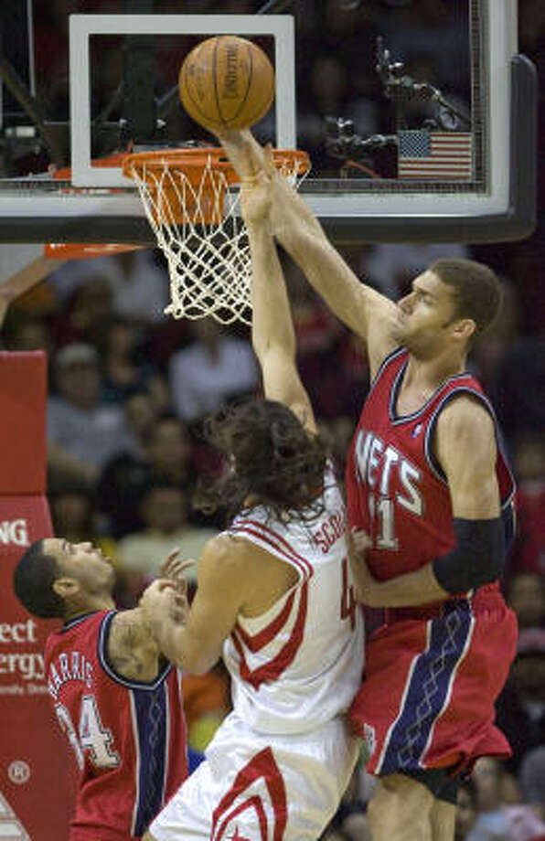 Nets center Brook Lopez tries to block a shot by Rockets forward Luis Scola. Photo: Steve Campbell, AP