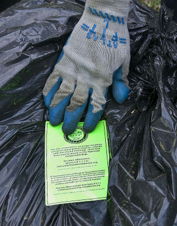 To remind residents of the new rules, city workers are placing notices on plastic bags with yard waste. Photo: James Nielsen, Chronicle