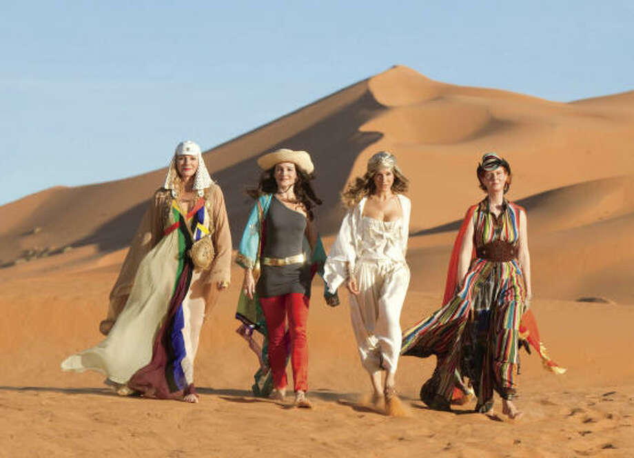 Kim Cattrall, from left, wears a Jean Paul Gaultier dress with a Balizza wrap and Horst hat (bag from Ralph Lauren); Kristin Davis wears an asymmetrical Alexander Wang top, Zac Posen pants and Bill Blass belt; Sarah Jessica Parker wears a Dior bustier over Ralph Lauren harem pants, Zara blouse and Philip Treacy turban; Cynthia Nixon wears a matching Hermès hat and dress with a Roberto Cavalli belt. Photo: CRAIG BLANKENHORN, RUNNING PRESS