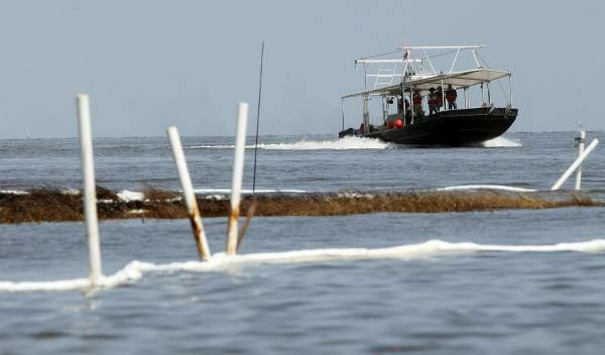 Fishermen motor past boom and oiled grasses in Barataria Bay, La. The BP spill began during spawning season for many fish, and most likely killed eggs and larvae, scientists said.