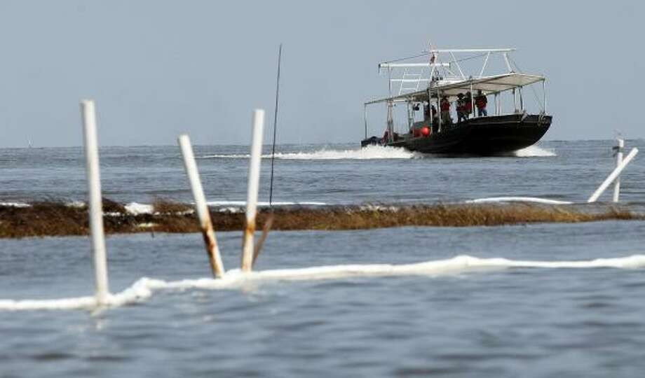 Fishermen motor past boom and oiled grasses in Barataria Bay, La. The BP spill began during spawning season for many fish, and most likely killed eggs and larvae, scientists said. Photo: Mario Tama, Getty Images