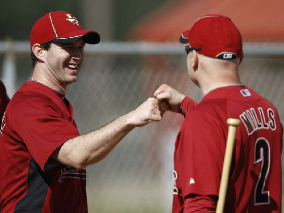 Manager Brad Mills fist-bumps pitcher Chris Sampson after a spring training drill. Photo: Julio Cortez, Chronicle