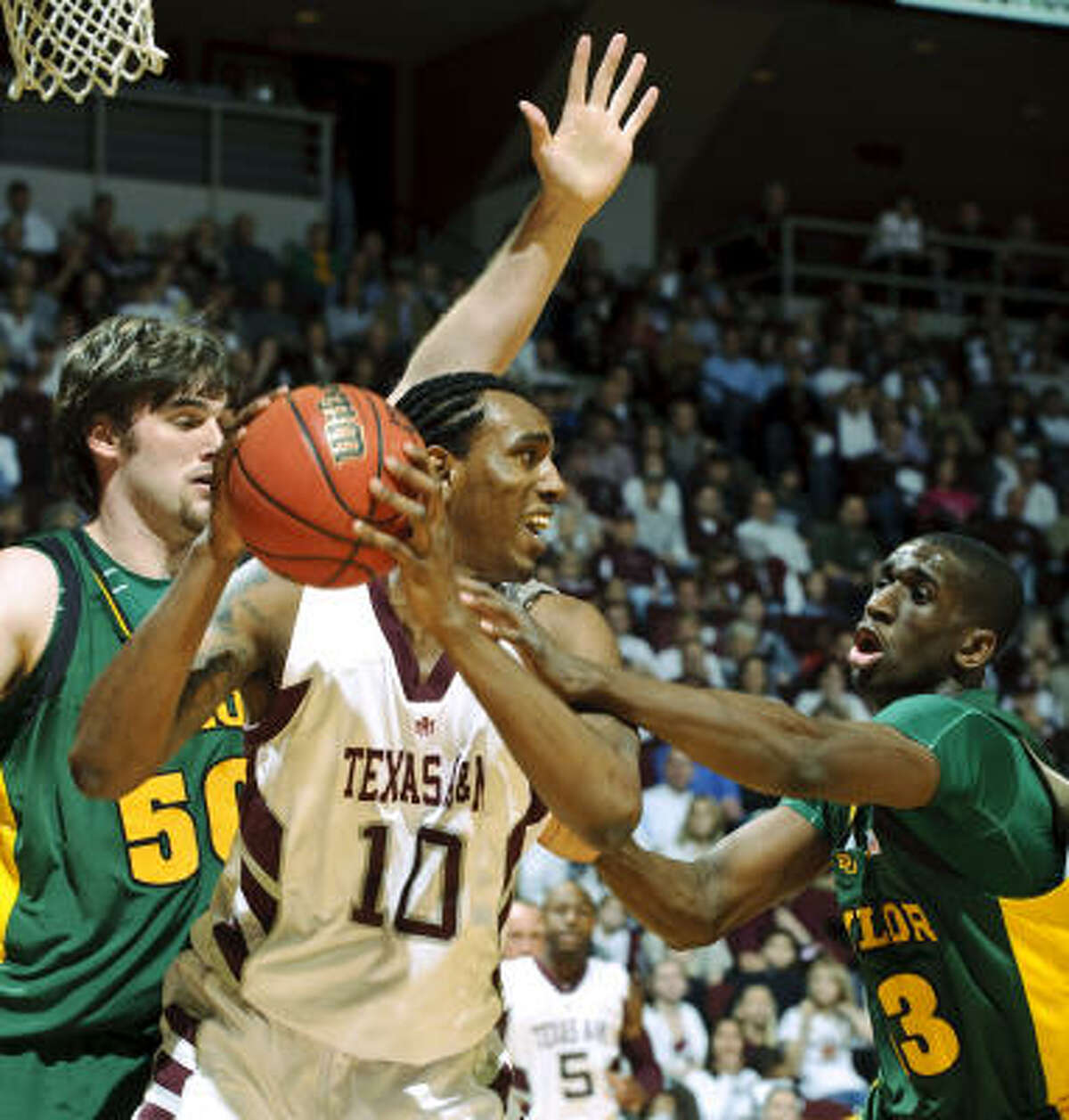 Texas A&M's David Loubeau (10) grabs a rebound away from Baylor's Josh Lomers (50) and Ekpe Udoh.