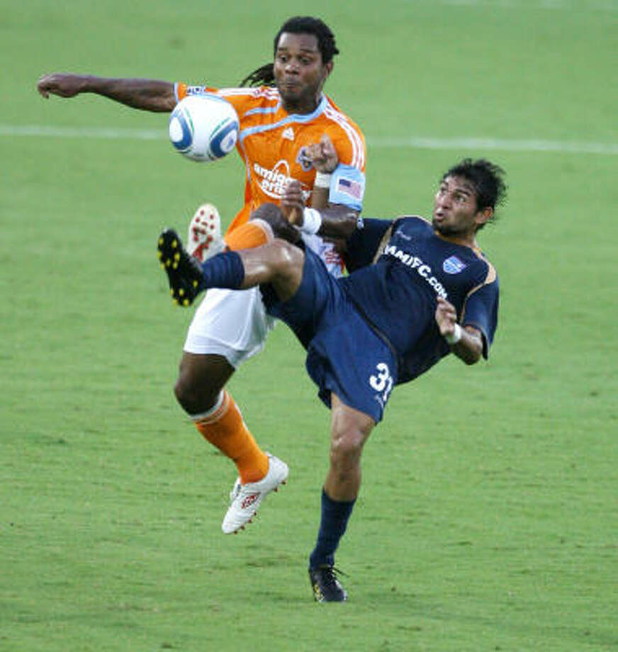 Adrian Serioux fights for the ball with Miami FC forward Paulo Araujo Junior in a 1-0 win for the Dynamo. Photo: Billy Smith II, Chronicle