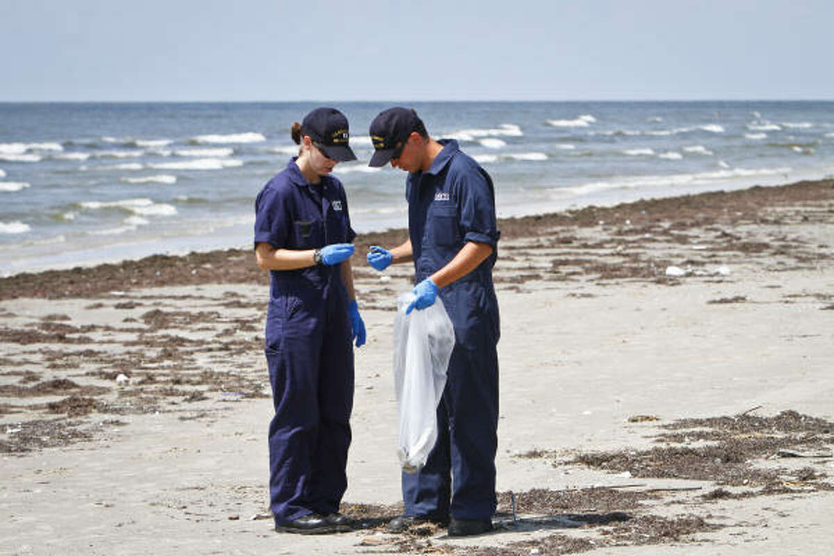 Coast Guard Lt. Jamie Koppi, left, and Marine Science Technician 3rd Class Andrew Garcia examine a Galveston beach on Tuesday. Most specimens were old and solidified.