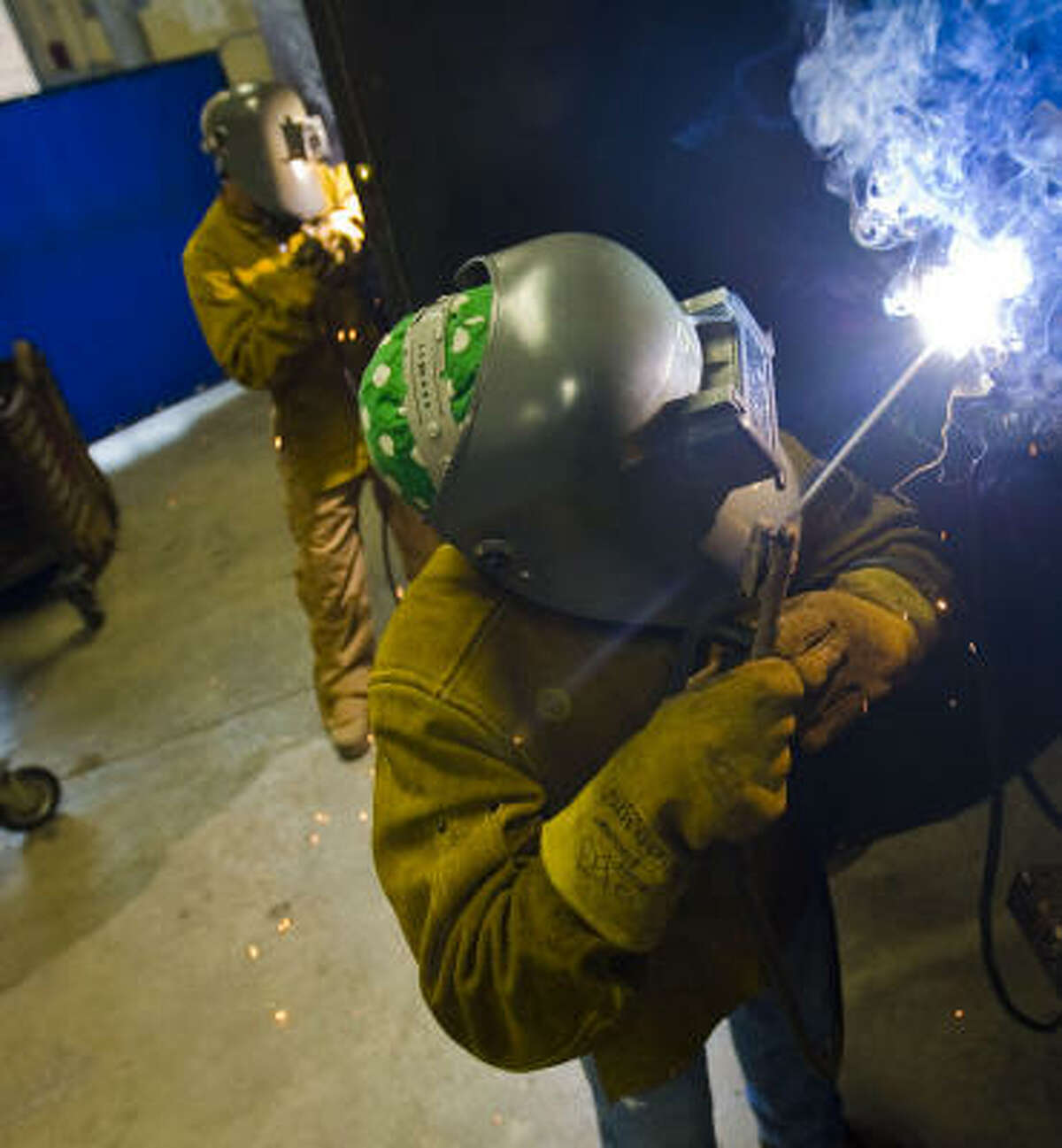 John Kalogeris, left, and Joe Magoffin practice their techniques at a certified welding program in, Columbia, Mo. The two 18-year-olds are among some 2,000 area students taking classes at the center instead of pursuing a four-year bachelor's degree.