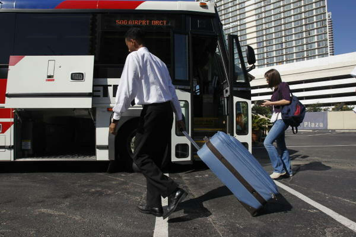 Hassen Mohammed, with Kennedi Taylor Concierges, helps a passenger with luggage Thursday at Metro's Airport Direct Plaza, 815 Pierce, for one of the 60 daily trips the service makes between downtown and Bush Intercontinental Airport.