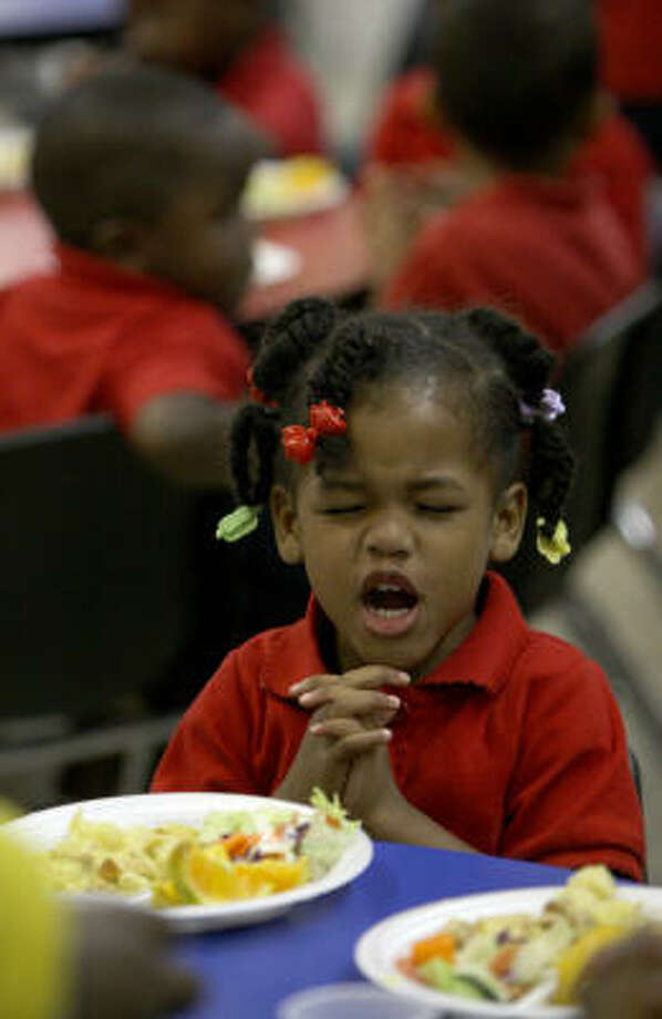 Pre-K student Jakeira Johnson, 3, prays before lunch at Yellowstone School. With limited federal funding, private, faith-based schools that cater to children from poor families are rare. Photo: Karen Warren, Chronicle