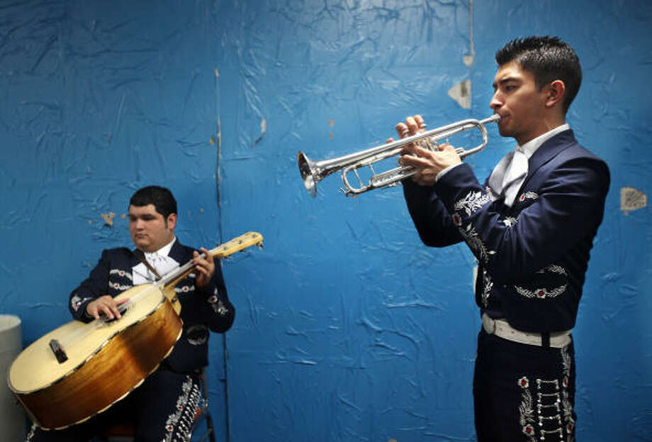 Fabian Rivera, left, and David Moreno, both with Mariachi Aztlan from the University of Texas-Pan American, warm up before performing To Cross the Face of the Moon at Talento Bilingue de Houston. Photo: Mayra Beltran, Houston Chronicle