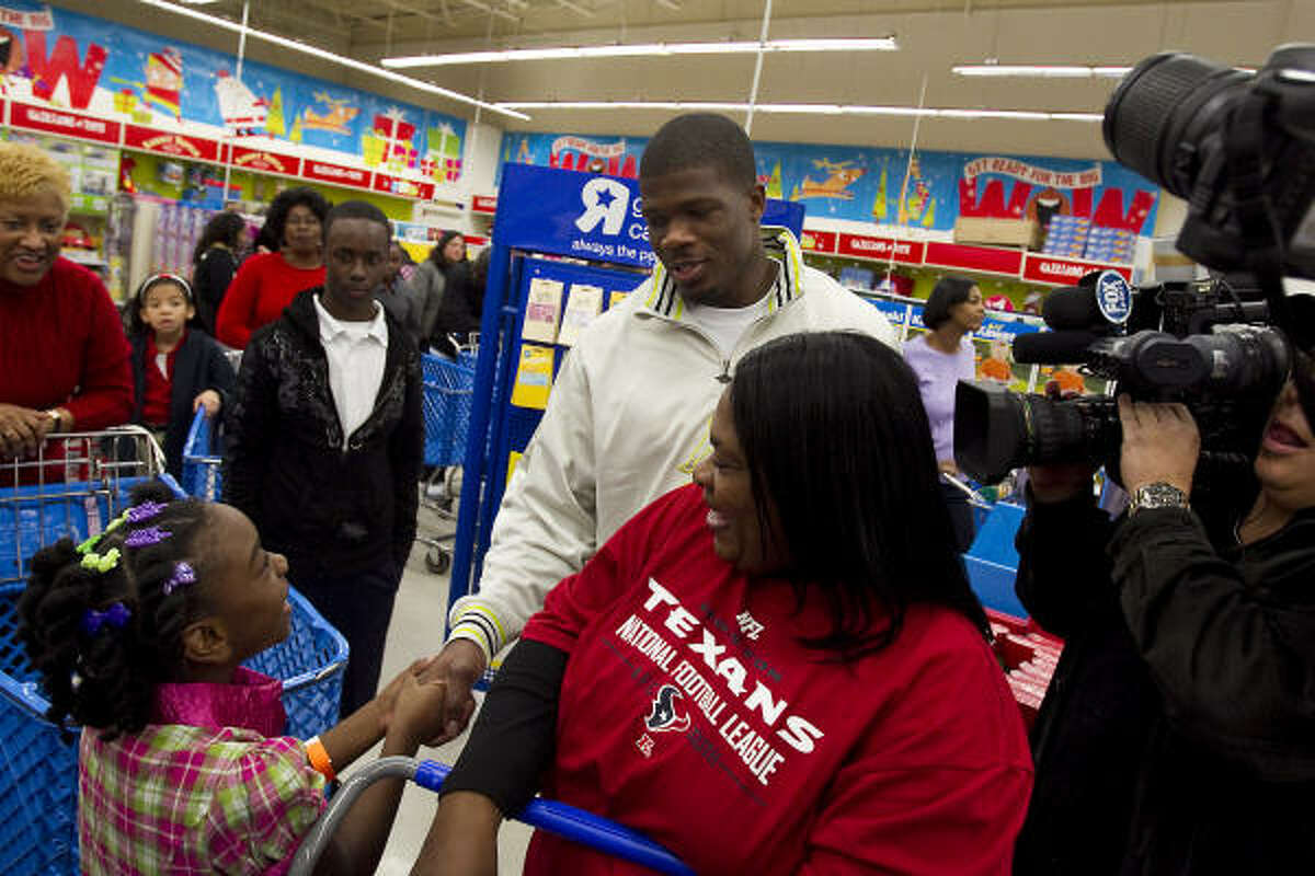 For the fourth straight year, Andre Johnson, center, hosted 12 children for a shopping spree at a local toy store.