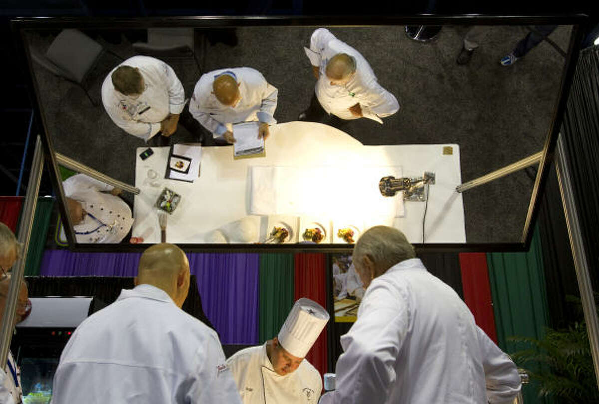Judges gather around the preparation table to watch chef Andrew Steiner of Lakeside Country Club prepare a dish in the Professional Chefs Association of Houston's competition Sunday during the 2010 Southwest Foodservice Expo at the George R. Brown Convention Center in Houston.