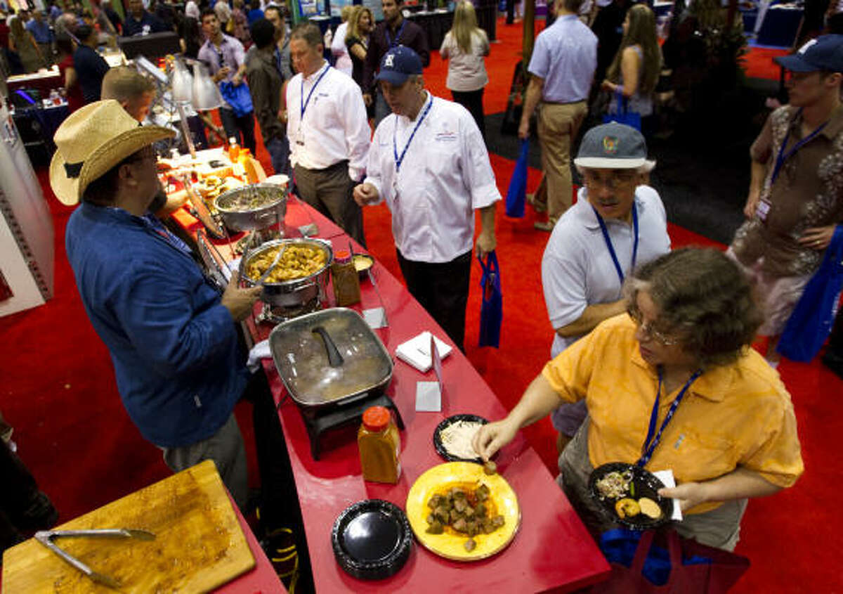 Patrons pass the McCormick's booth during the expo, which kicked off Sunday and ends Tuesday. The event explores food trends, products and technology.