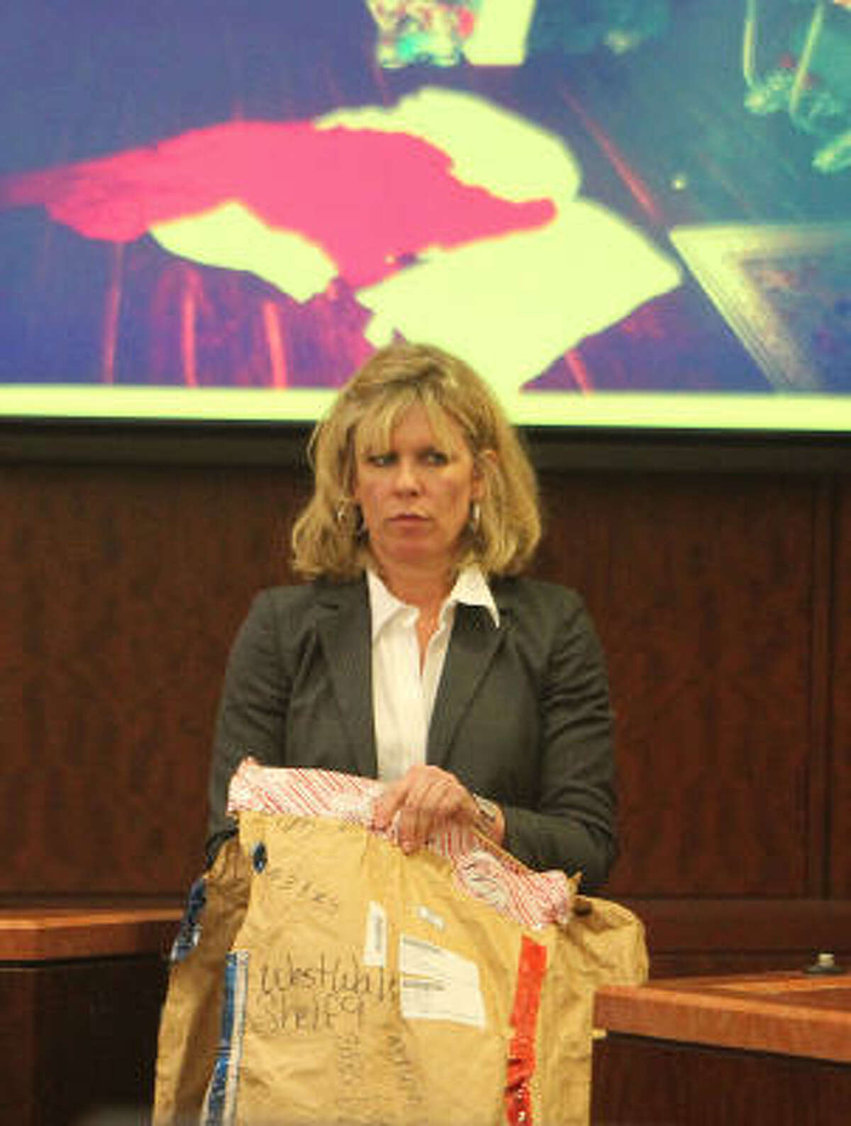 County prosecutor Colleen Barnett produces a bag of evidence in during the trial of Lucas Coe on Thursday.