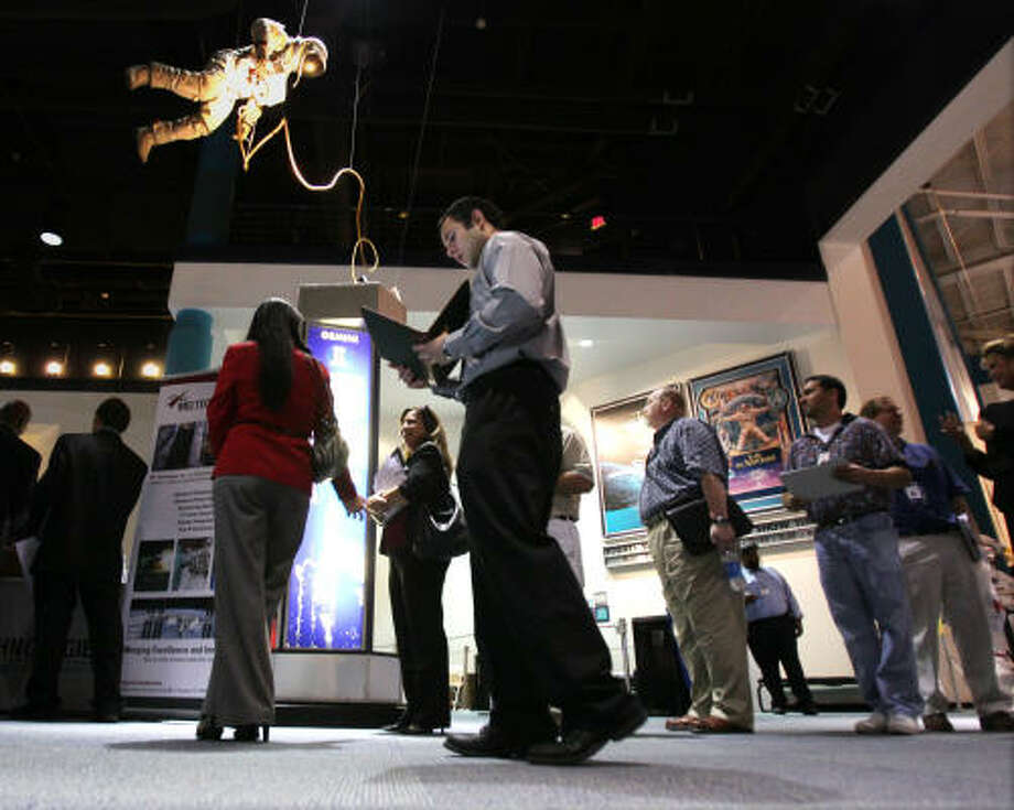 Omar Monterrubio looks over his resume as he walks by a line with other job seekers at a Recruiting Expo held by Workforce Solutions and NASA.at Space Center Houston, Tuesday, September 14, 2010.  Due to upcoming NASA transition activities, hundreds of highly skilled professionals are currently seeking new employment opportunities.  Monterrubio who recently graduated with a Mechanical Engineering was attending the fair in hopes of finding a job in his field. Photo: Billy Smith II, Chronicle