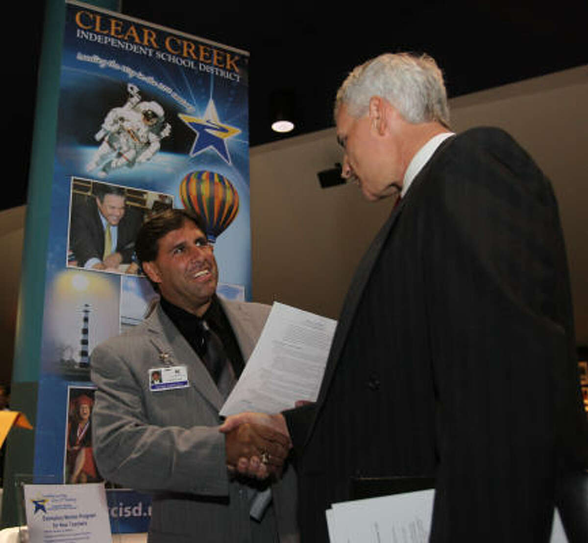 Lonnie Leal with Clear Creek Independent School District talks with former NASA contractor Tom Underkircher during a Recruiting Expo held by Workforce Solutions and NASA/Johnson Space Center at Space Center Houston on Tuesday.