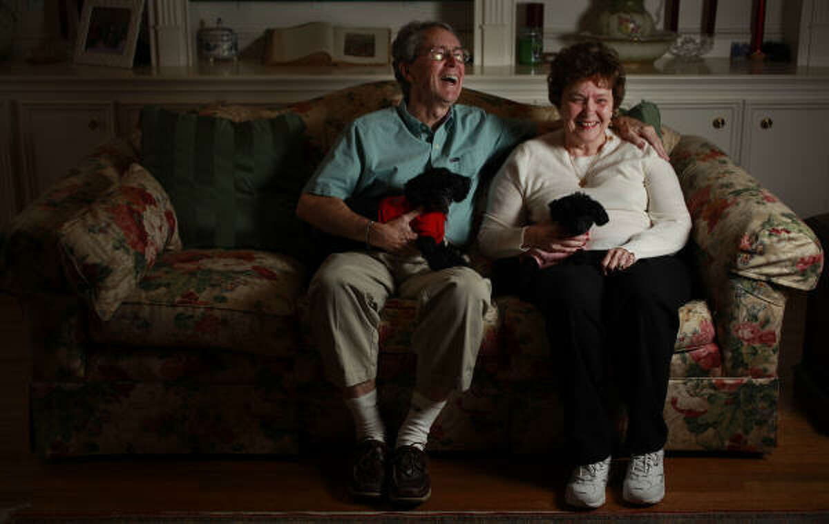 Bill and Anne Cunningham sit in their West University Place home with toy poodles Winston and Abby.