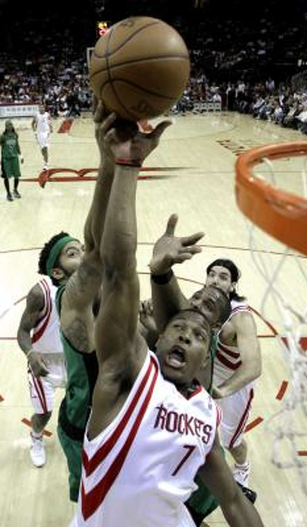 Rockets guard Kyle Lowry goes up for the ball against Celtics forwards Rasheed Wallace, left, and Glen Davis.