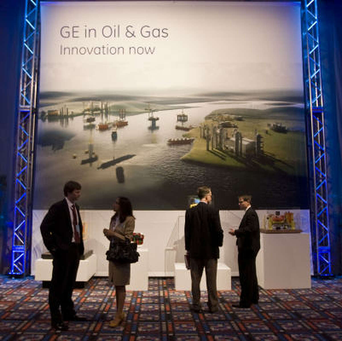 With a GE display as the backdrop, several people attending the company's meeting talk things over Wednesday at the George R. Brown Convention Center.