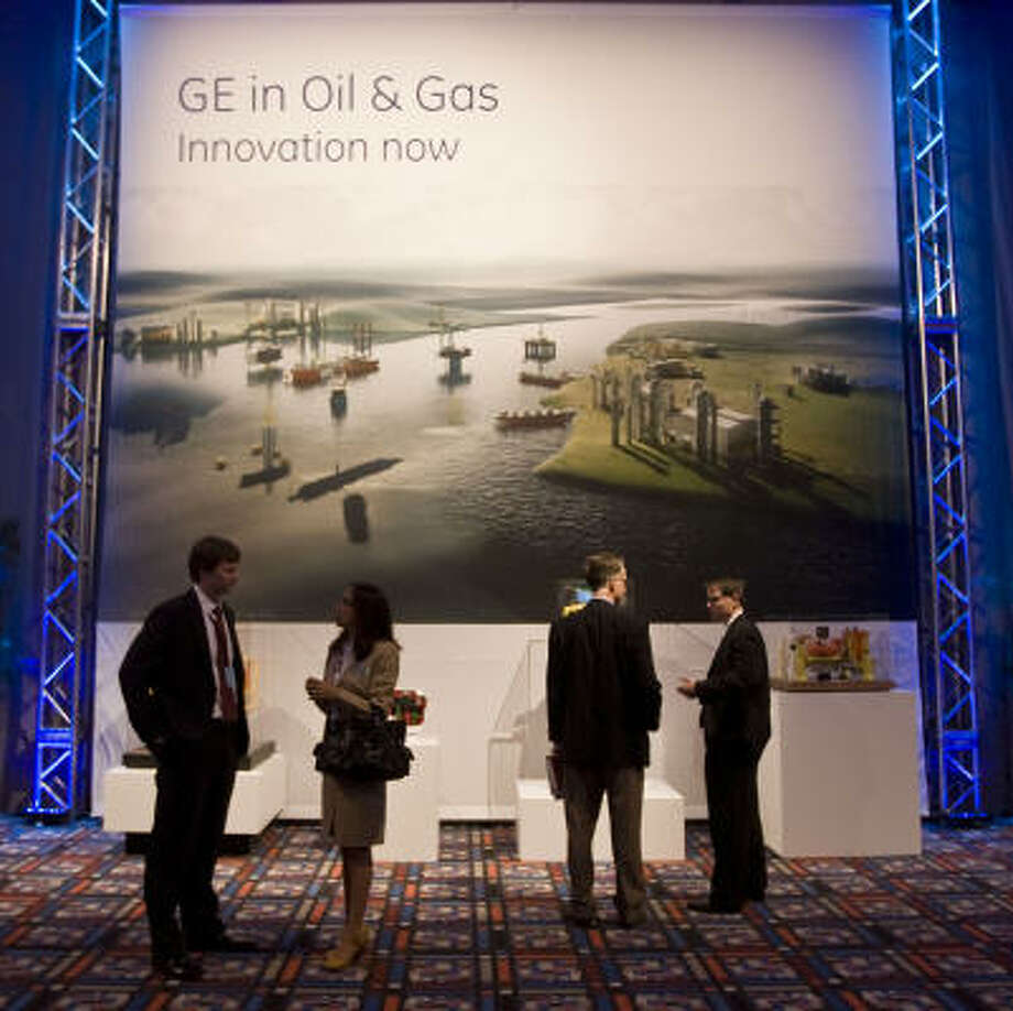 With a GE display as the backdrop, several people attending the company's meeting talk things over Wednesday at the George R. Brown Convention Center. Photo: James Nielsen:, Chronicle