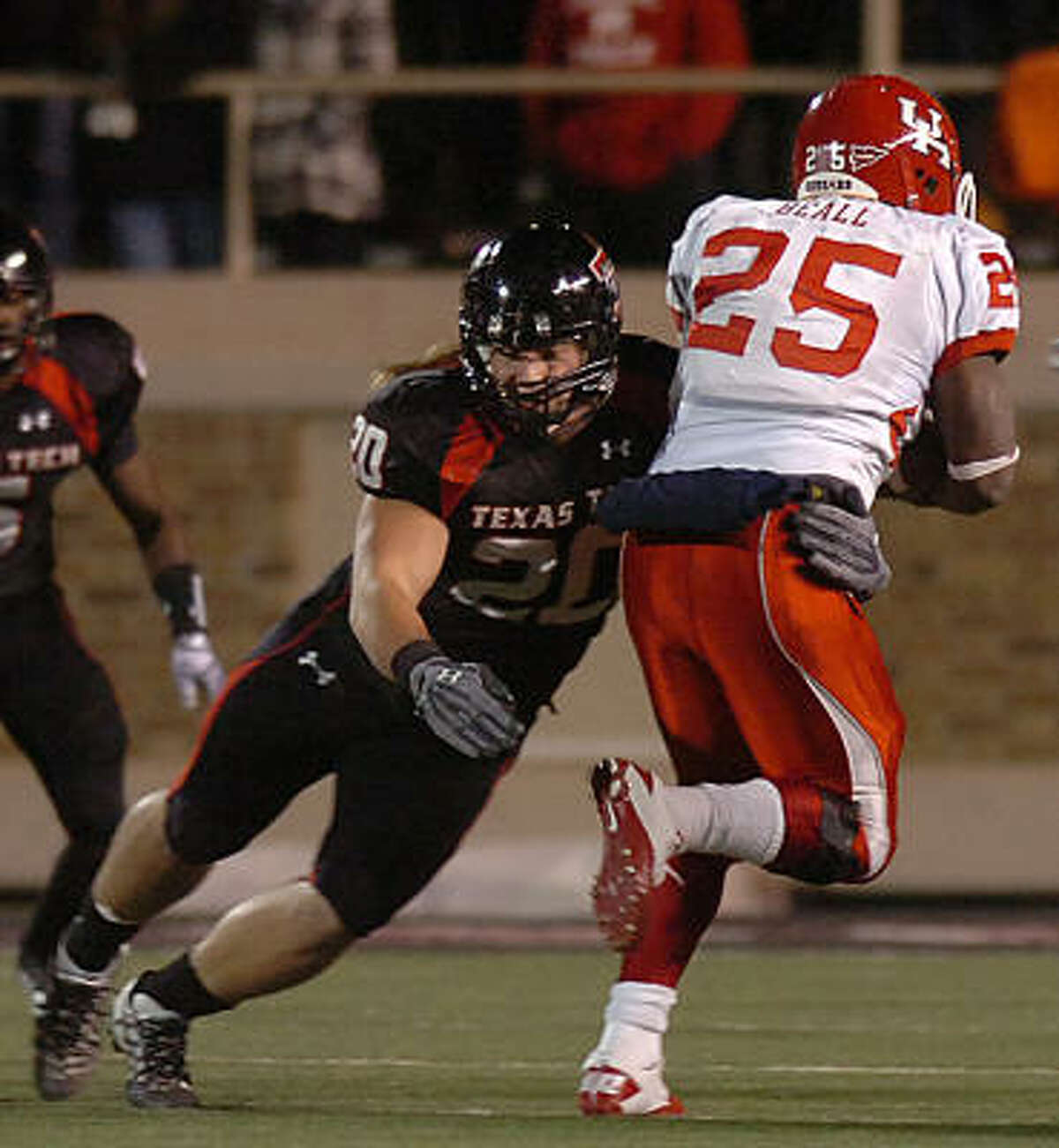 Texas Tech's Bront Bird, left, stops UH running back Bryce Beall during Saturday's game.