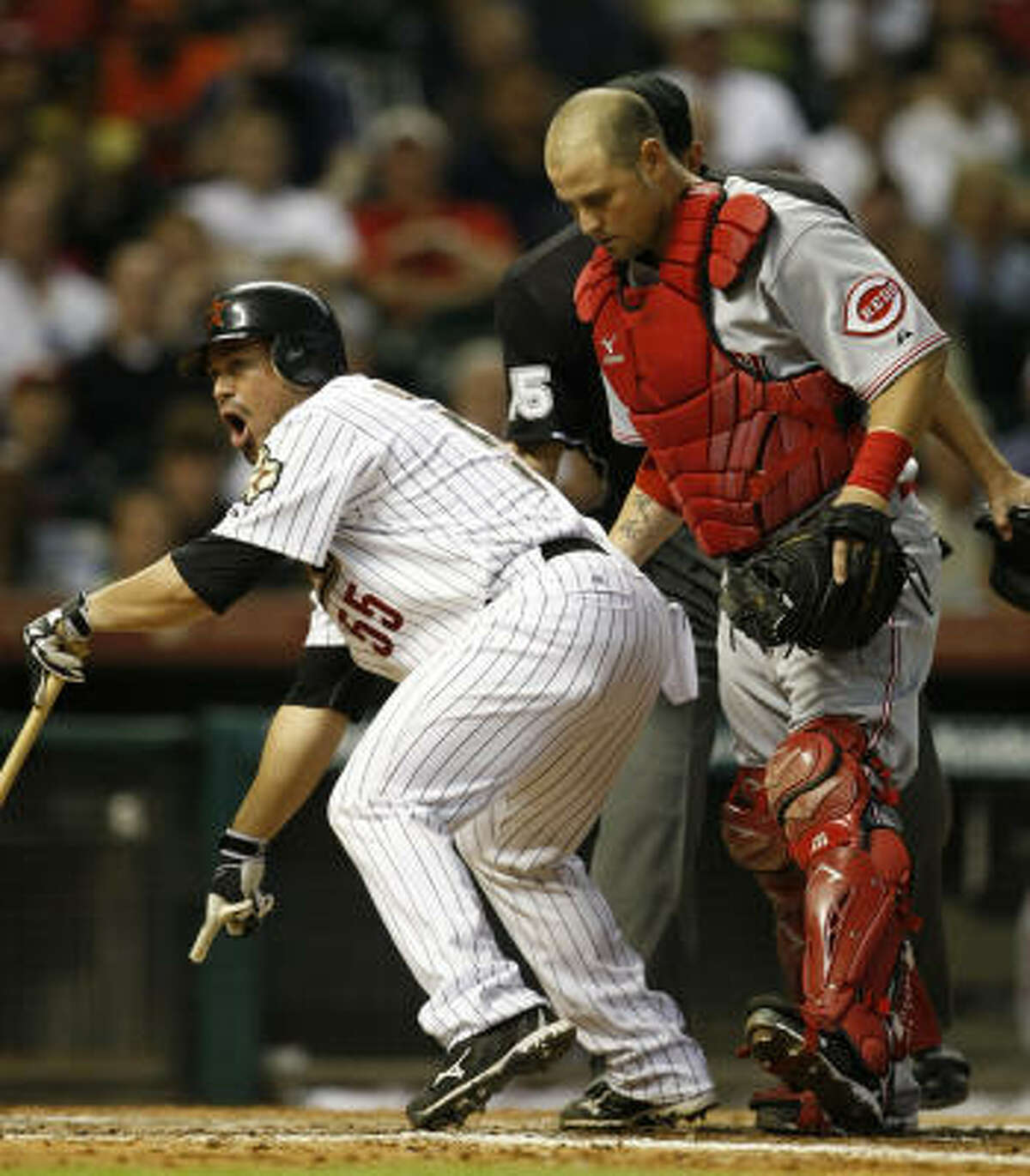 Astros catcher Humberto Quintero, left, points to the ground where he claims his foul ball hit prior to being tagged out by Reds catcher Ramon Hernandez in the seventh inning.