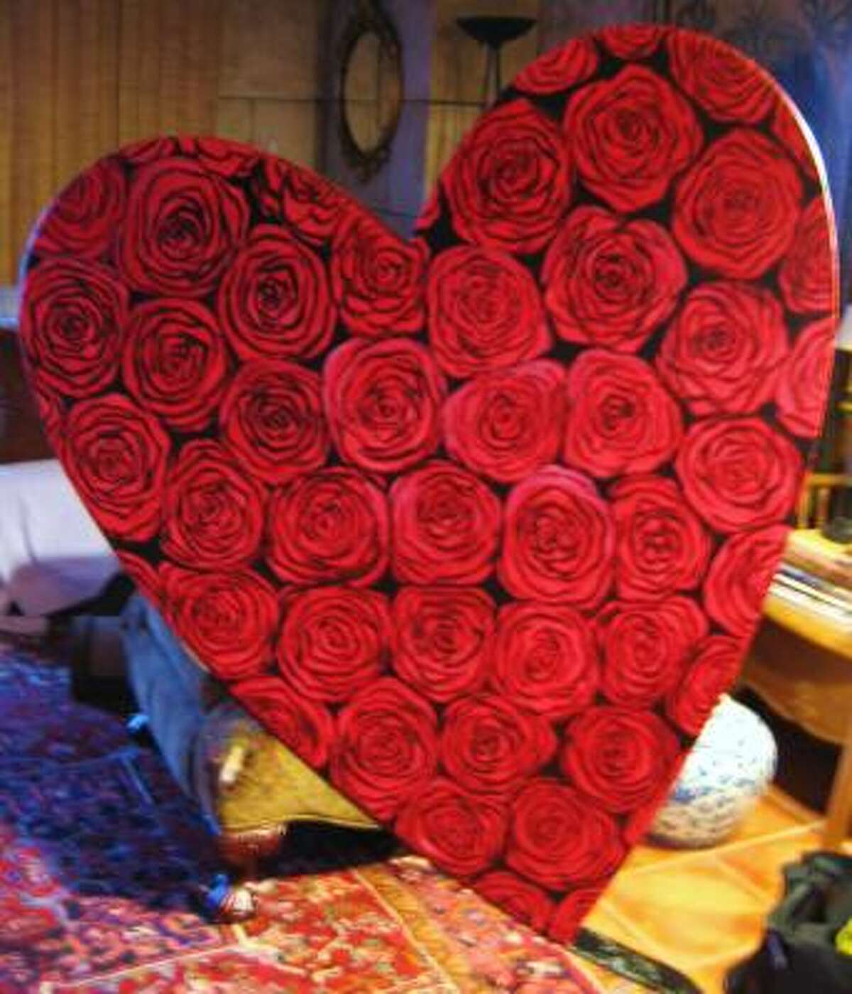 ROSY WORK: Artist Kermit Eisenhut created his Heart Deco piece, left, with roses. The work is one of 10 pieces that will be unveiled May 25 as part of an art show to benefit the American Heart Association.