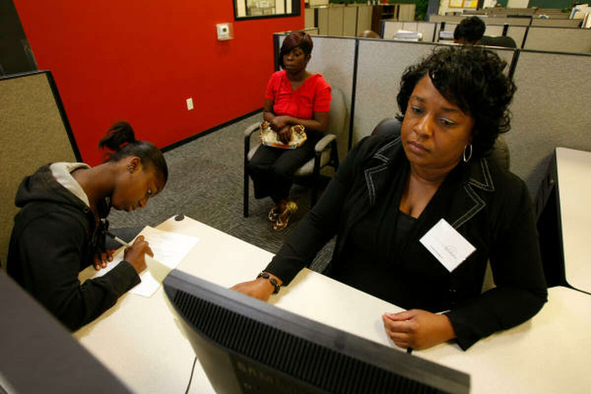 Raven Roberson, 16, fills out an application at Workforce Solutions with intake specialist Leslie Bourgeois, right, and mother Martena Ursin this week. Roberson, who attends Reagan High, is among many students looking for a summer job.