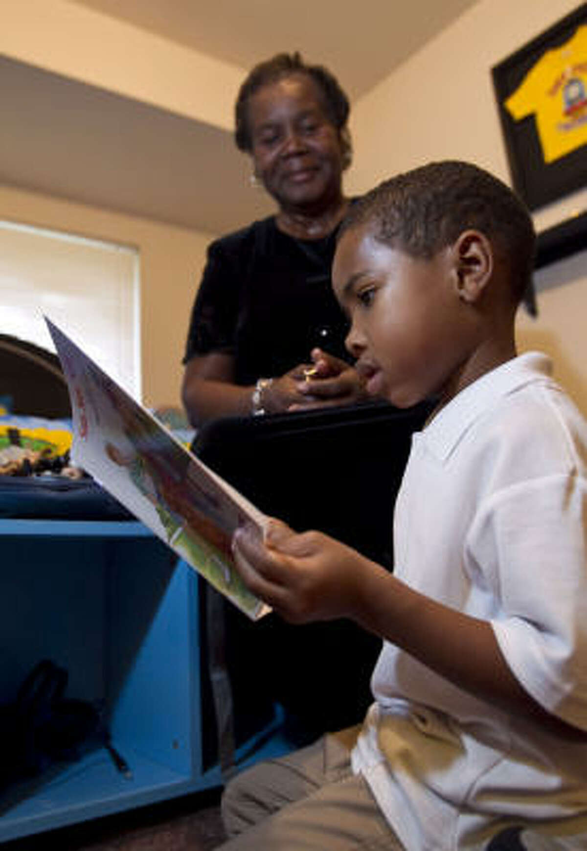 Five-year-old Thomas DuBose reads to his grandmother Doris Marie Thomas at her home Friday in Houston.
