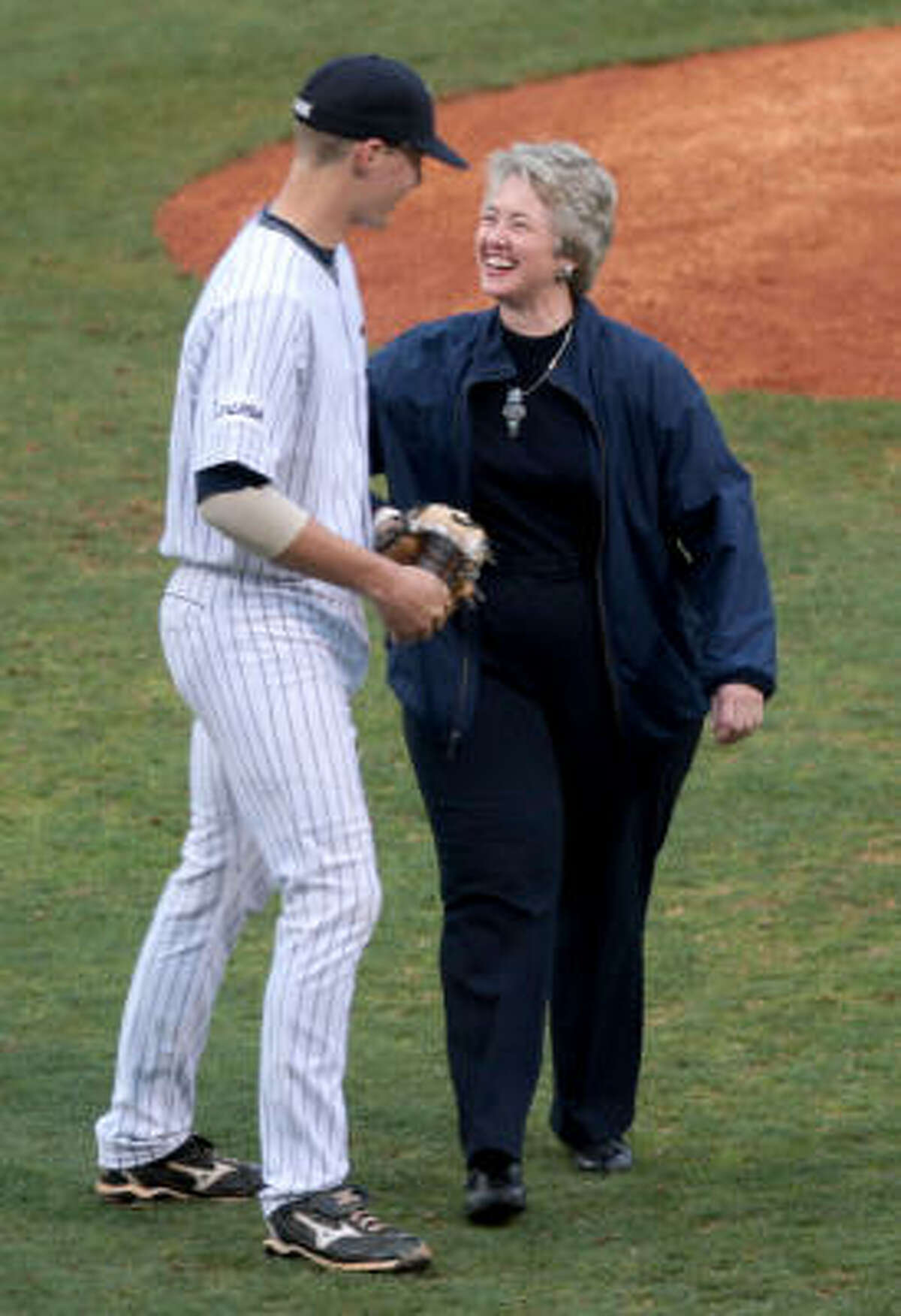 Houston mayor Annise Parker, a Rice alum, shakes hands with Rice's Geoff Perrott after he caught Parker's opening pitch.