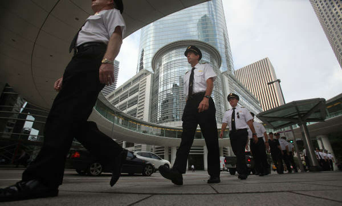 """Continental pilots walk from the airline's headquarters to the Hyatt Regency downtown. A banner said: """"Continental may be United but not without the pilots."""""""