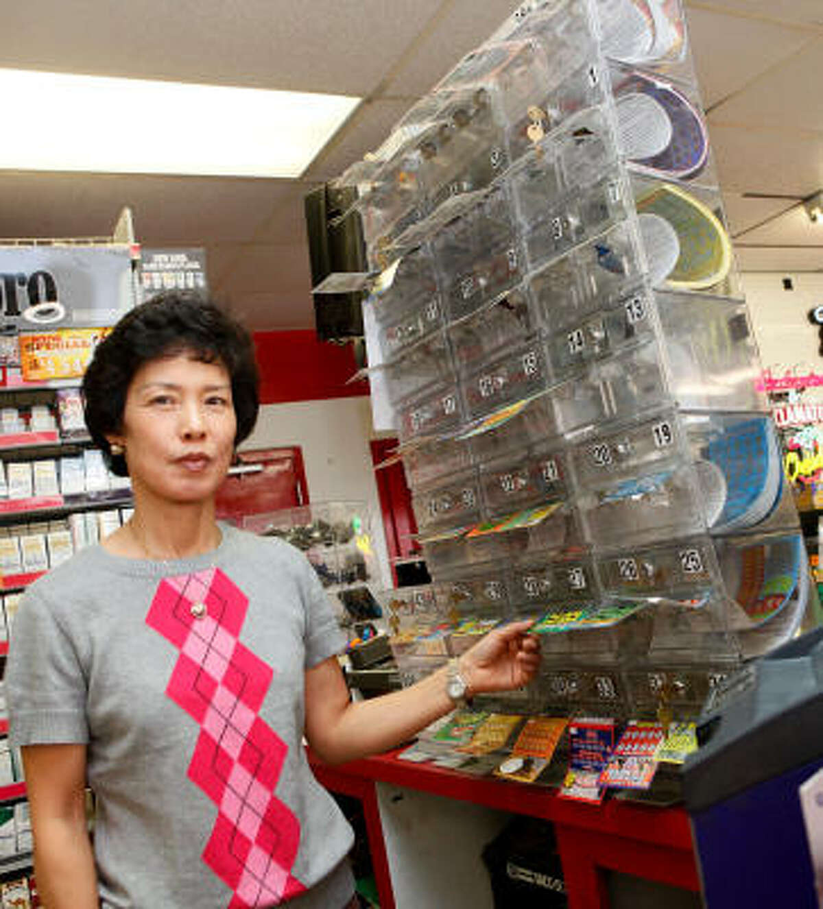 Sun Bae, owner of the Times Market, stands next to the lottery tickets at her store in Bishop.