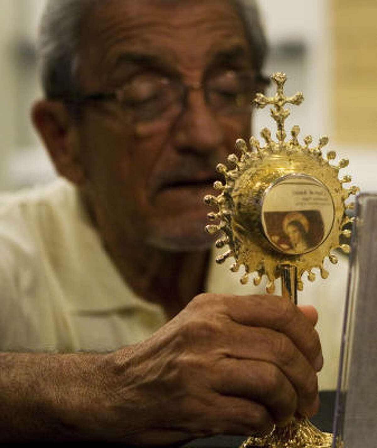 Rudy Salinas kneels down to look at a relic of St. Clare of Assisi during a display of the