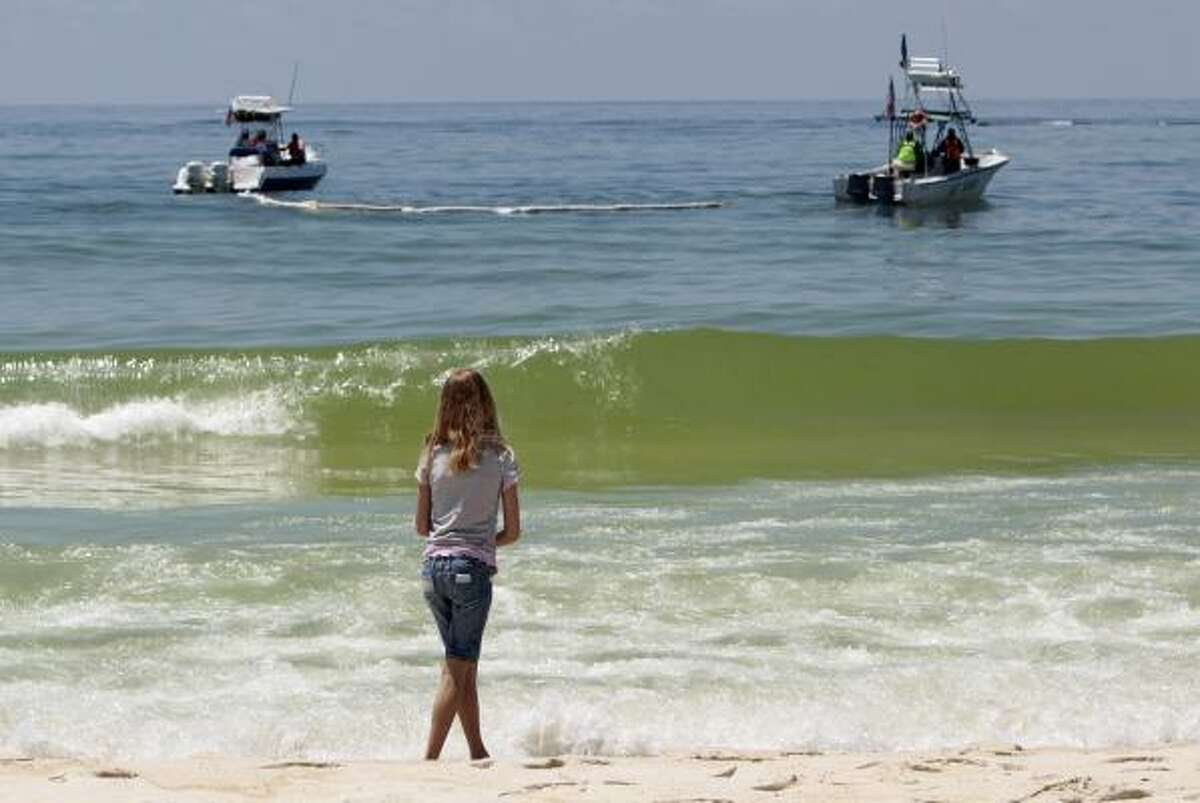 Skyla Cromley, 8, of Pensacola, Fla., watches boats skim oil just off Pensacola Beach on Friday. Much of the oil that washed up has been removed, and the beach was reopened. A storm could stop all collection efforts and allow the well to flow unchecked.
