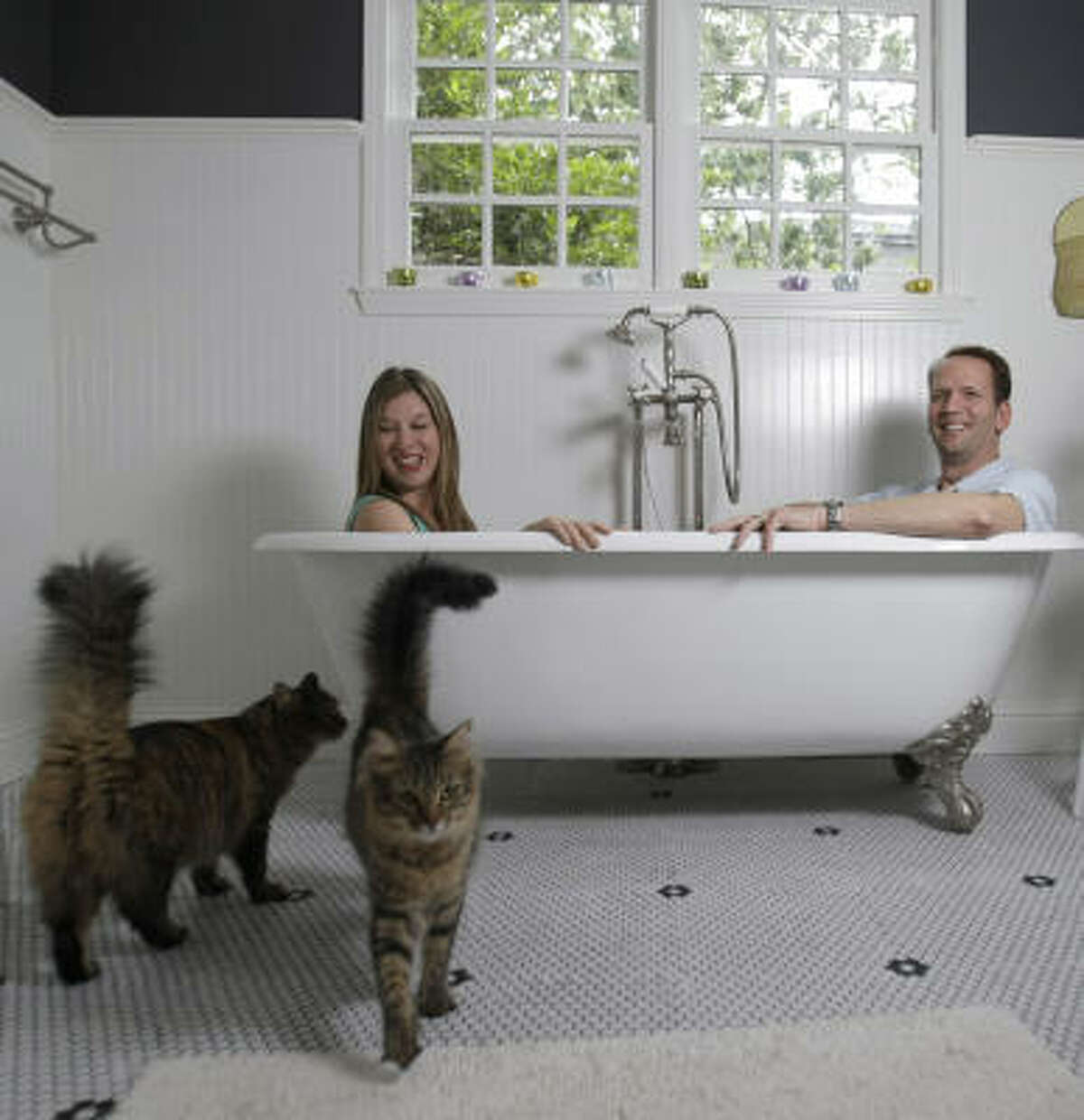 Dwayne and Sarah Van Wieren try out their new tub as their cats, Ron and Nancy, check out the tile. The professional couple got a no-money-down loan in West U.