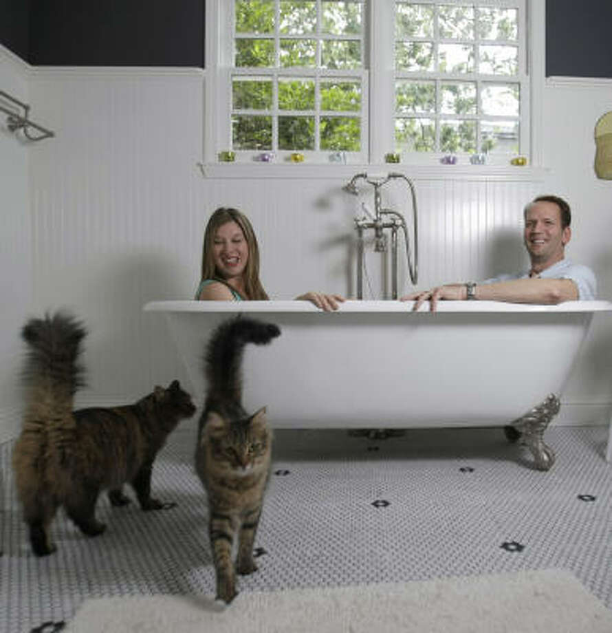 Dwayne and Sarah Van Wieren try out their new tub as their cats, Ron and Nancy, check out the tile. The professional couple got a no-money-down loan in West U. Photo: Karen Warren, Chronicle