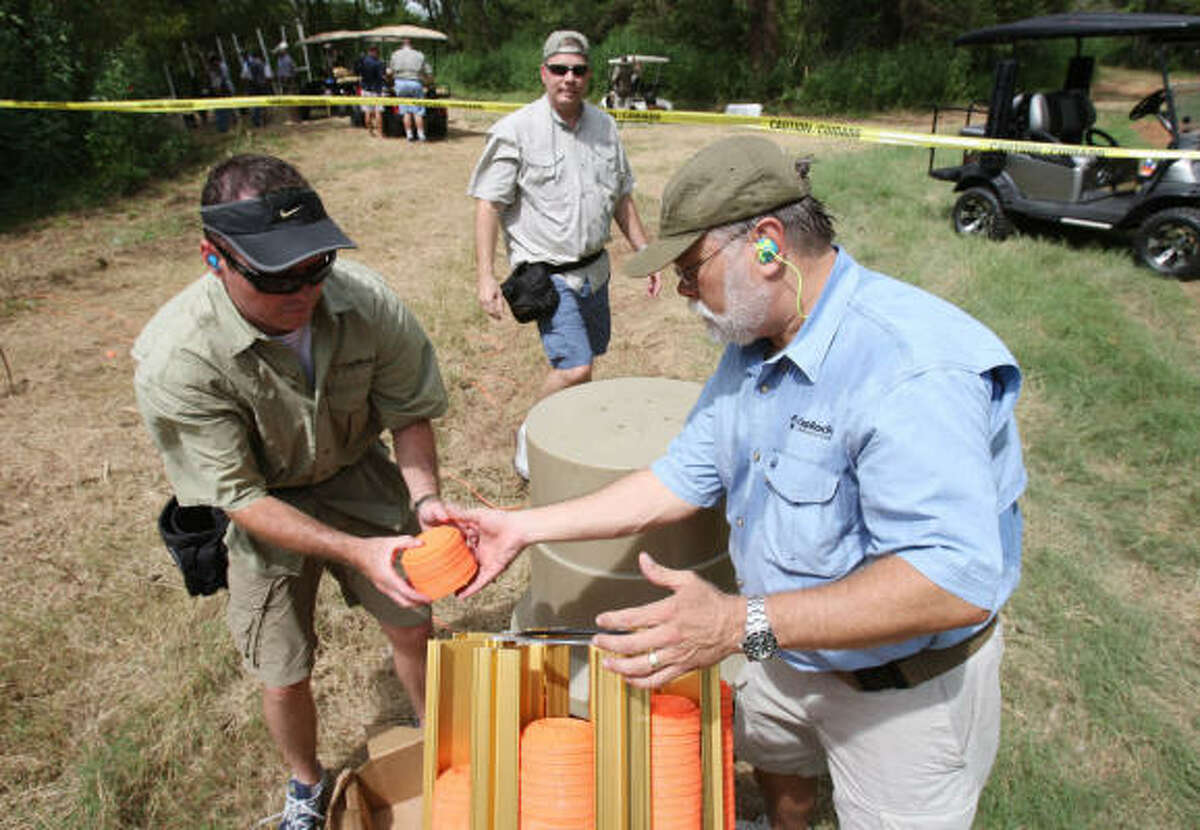 Travis Betke, right, and Steven Newstead load pigeon clays on a machine that propels them in the air Friday as the team took a moment to help in preparation for clay shooting.