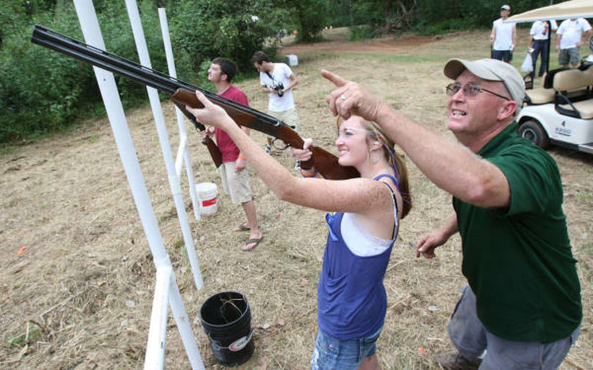 : Alicia Revette, of State Line Miss., whose father, Dewey Revette, died during the Deepwater Horizon accident, gets help shooting clay pigeons from Jason Menke, of Briley Manufacturing, in preparation for a clay shooting tournament.