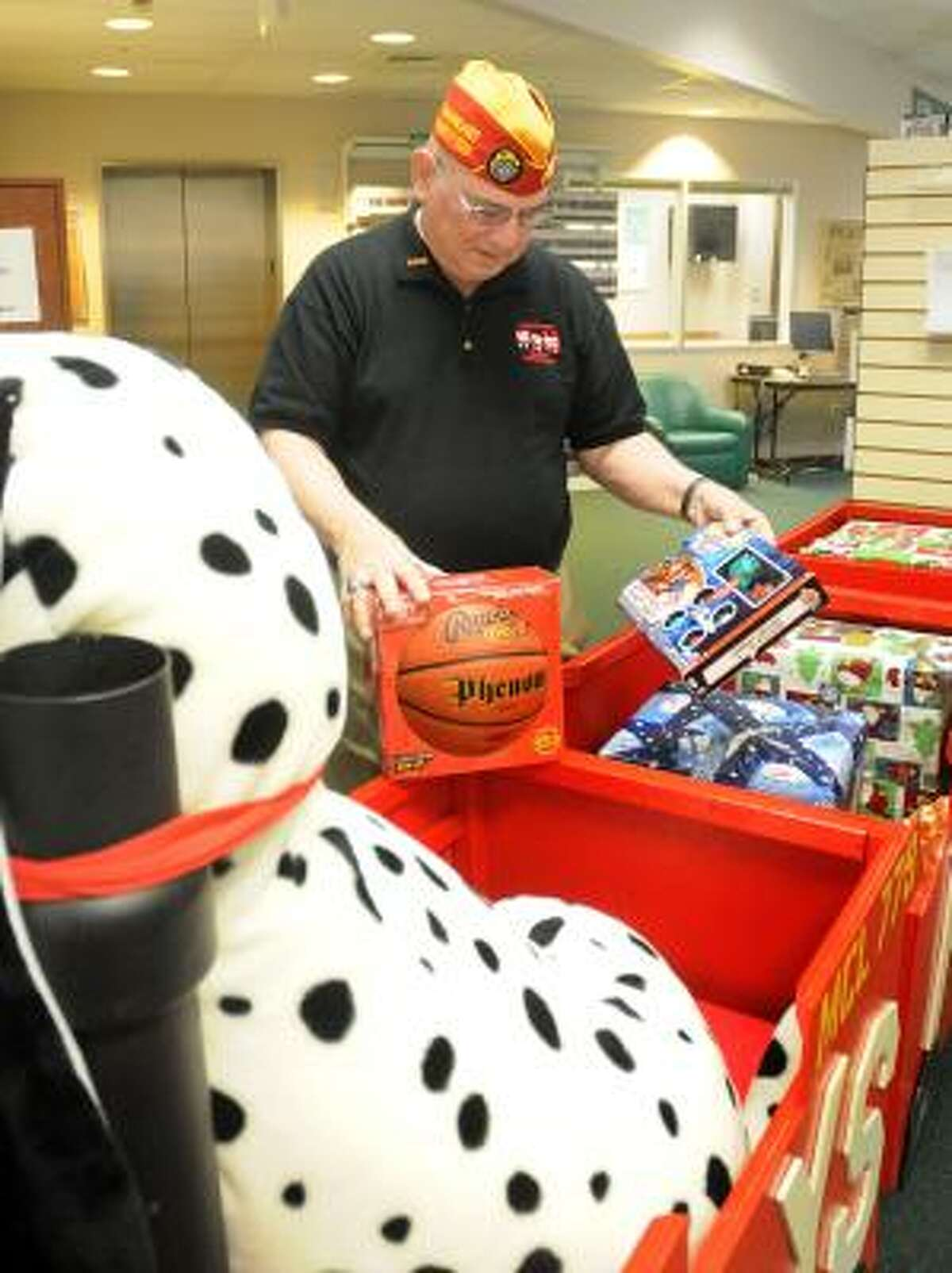 DAVID HOPPER: FOR THE CHRONICLE FILLING UP: Bob Quinn, Eastex Marine Corps League Toys for Tots coordinator, checks donated toys at the Conroe Central Library Toys for Tots collection area.