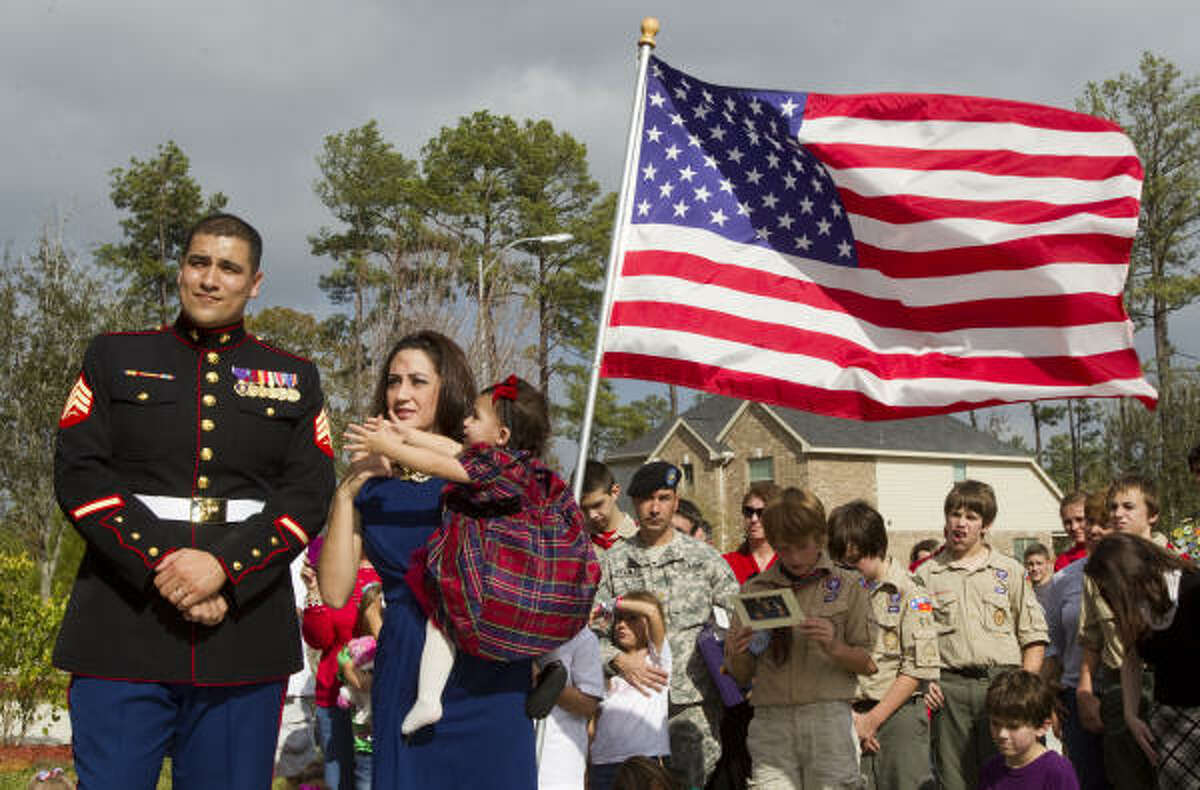Retired Marine Sgt. Eusebio Collazo, with his wife, Karla, and daughter, Gabriella, accept a new home Tuesday during a ceremony in the Eagle Springs subdivision in Humble. The Marine, who earned a Purple Heart in Iraq, suffered a traumatic brain injury when his barracks was attacked by insurgent mortar fire.