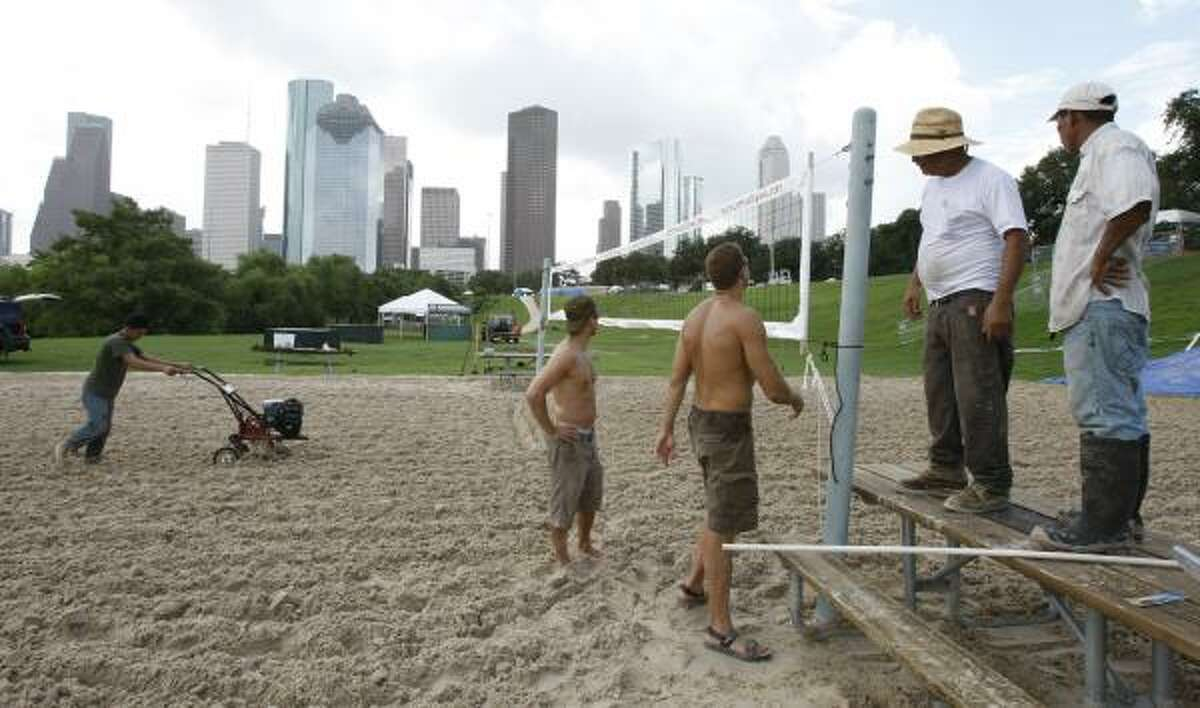 Carlos Hernandez tills the sand court Saturday while others set the net for the state volleyball championships to be held during the annual July Fourth celebration on Sunday at Eleanor Tinsley Park. The site was underwater after Friday's flooding.