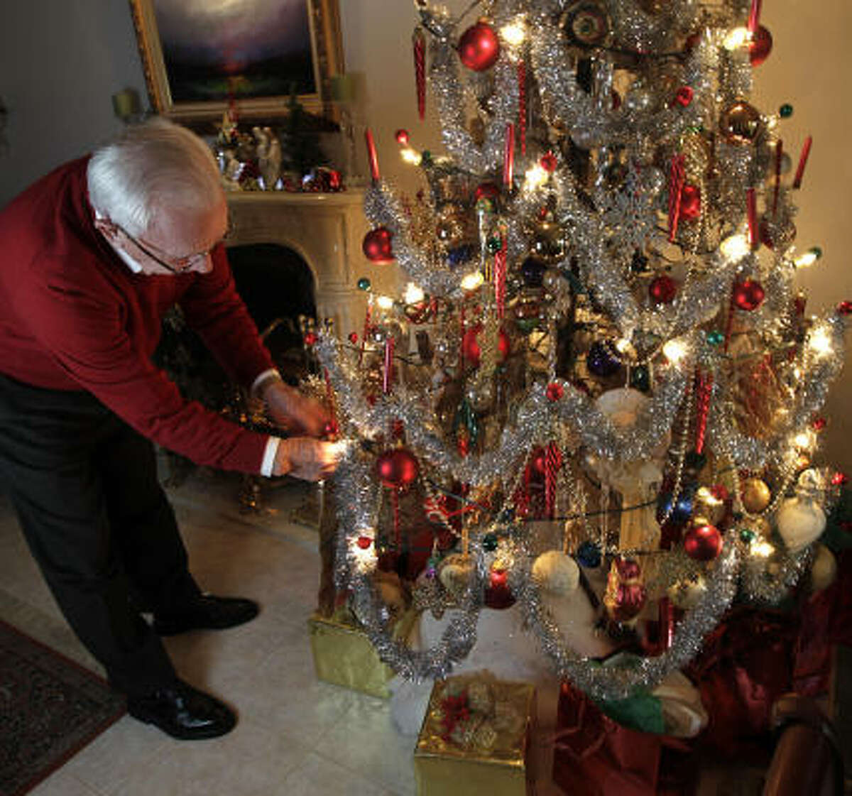 Lynn Ringh, 78, the caretaker of his family's 100-year-old artificial Christmas tree, adjusts an ornament on it at his home in Houston.
