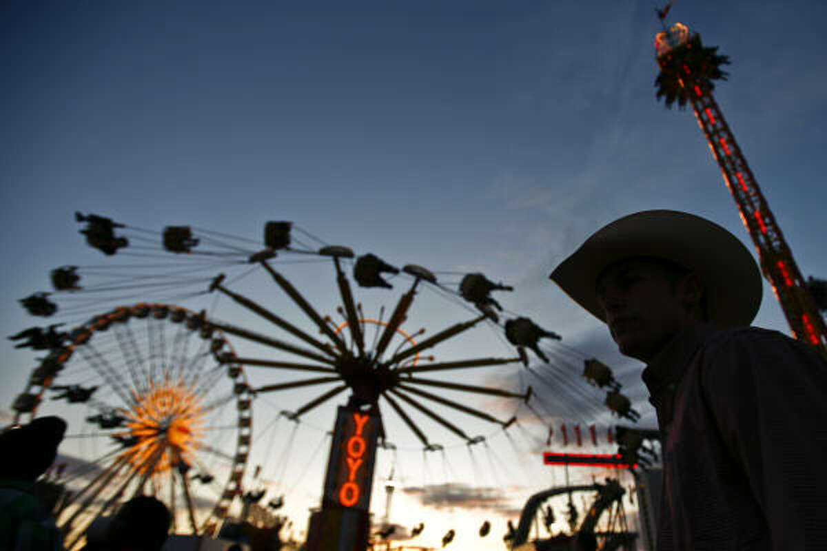 Mathew Wolfe walks in the carnival area as the rides take a few final whirls before putting the rodeo to bed.