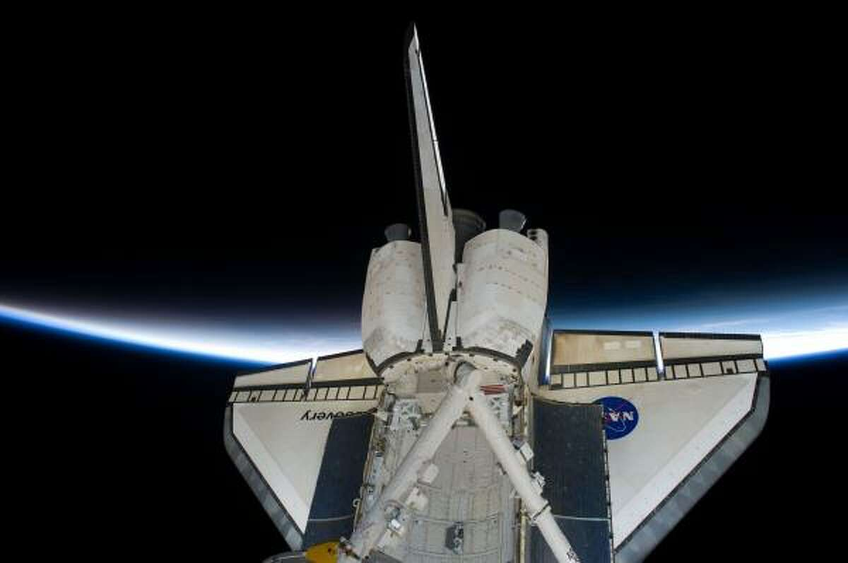 Discovery is seen against a backdrop of Earth's atmosphere while docked with the International Space Station. Unlike previous shuttle departures, there was no live TV from Discovery on Saturday because the main antenna failed after launch. The shuttle is to land in Florida on Monday.