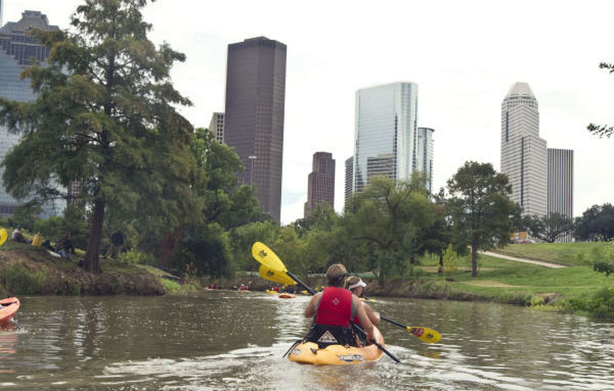GO WITH THE FLOW: Kayakers paddle Buffalo Bayou on Buffalo Bayou Shuttle Service's Skyline Tour.